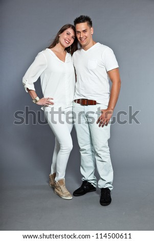 Diverse young happy couple together. Dressed in white. Laughing and having fun. Studio shot. Isolated on grey background.
