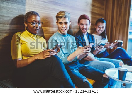 Diverse young people in casual wear holding modern smartphones in hands and messaging in online chat using internet connection. Multicultural bloggers communicating with friends. Millennials addiction