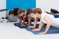 Diverse young people working out in a gym together in a class doing push up in a healthy lifestyle and fitness concept