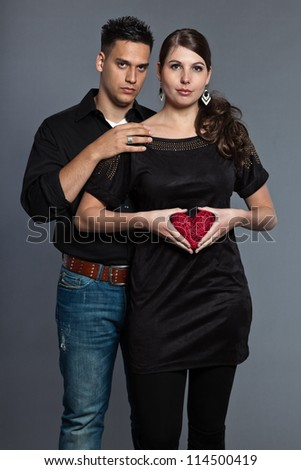 Diverse young serious couple together. Dressed in black. Holding red heart. Studio shot. Isolated on grey background.