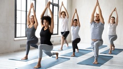 Diverse young sporty people doing Warrior one exercise at group lesson, practicing yoga in modern fitness center, standing in Virabhadrasana pose, working out with African American female instructor