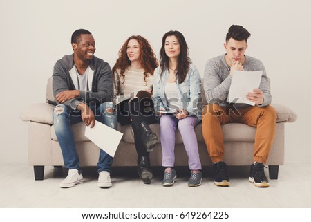 Diverse young students preparing for exam, sitting on sofa in living room and studying, studio shot - Shutterstock ID 649264225