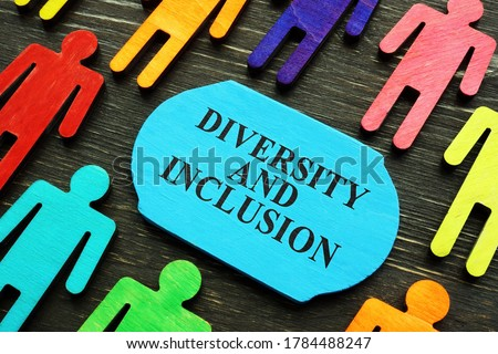 Diversity and inclusion phrase and colored wooden figurines.