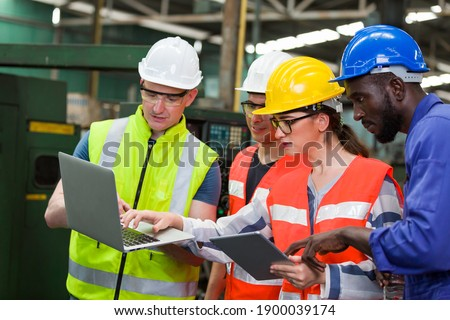 Diversity factory worker working with computer laptop in factory. Male and female worker wearing safety uniform, helmet and gloves at work factory. Group of worker working at factory