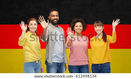 diversity, immigration and people concept - international group of happy smiling men and women waving hands over german flag background ストックフォト ©