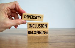 Diversity, inclusion and belonging symbol. Wooden blocks with words 'diversity, inclusion, belonging' on beautiful white background. Male hand. Diversity, business, inclusion and belonging concept