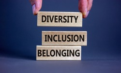 Diversity, inclusion and belonging symbol. Wooden blocks with words 'diversity, inclusion, belonging' on beautiful grey background. Male hand. Diversity, business, inclusion and belonging concept.