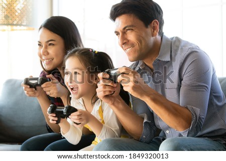 Diversity multiracial Caucasian and Asian family father, mother and daughter sitting together on sofa and playing computer game together with fun and happiness. Idea for generation time sharing Photo stock ©