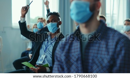 Diversity of corporate people in masks participating in conference meeting business seminar, raising hands to ask the speaker. Presentation. Social distance. Coronavirus.