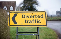 Diverted traffic sign with left arrow. Yellow UK road sign closeup showing a diversion or detour.
