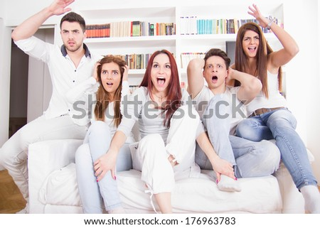 divided friends watching game on tv cheering for different teams