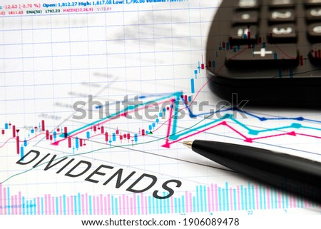 DIVIDENDS text on documents with graphs, charts, calculator, pen, financial concept background. Photo stock ©