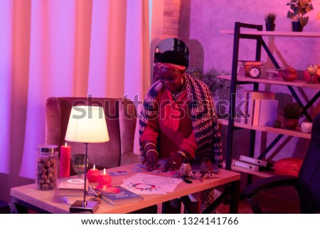 Divination accessories. African american plump fortune-teller wearing huge earrings standing near the table with divination accessories