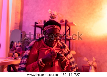 Divination in process. African american plump fortune-teller wearing big rings working in a divination salon