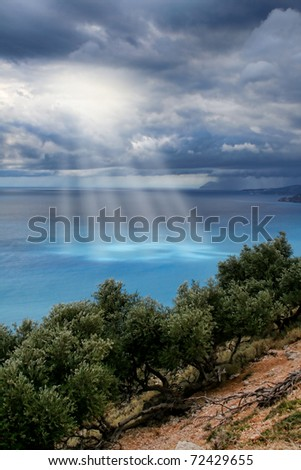 Divine light beams through storm clouds sky above turquoise sea