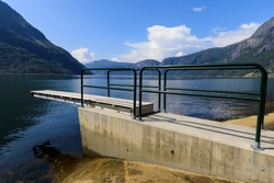 Diving board on the shore of a spectacular Norwegian fjord, with calm water and a mountain backdrop, on a beautiful sunny day in Summer, Eidfjord, Hardangerfjord, Hordaland, Norway