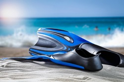 Diving fins on the shore of the blue sea