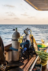 Diving gear with tanks, BCDs,  regulators, weight belts assembled, on a diving boat with sea view in the background, Red Sea, Sudan, portrait view.
