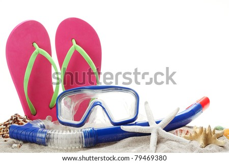 Diving goggles,snorkel and flip flops on sand.