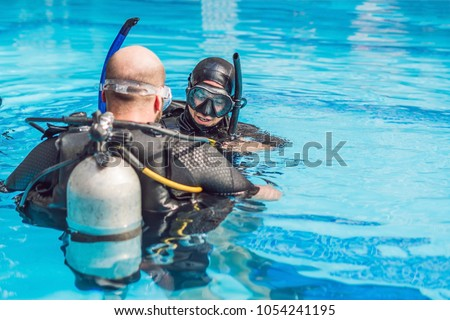 Diving instructor and students. Instructor teaches students to dive #1054241195