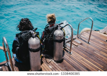 Diving lesson in open water. Scuba diver before diving into ocean. #1338400385