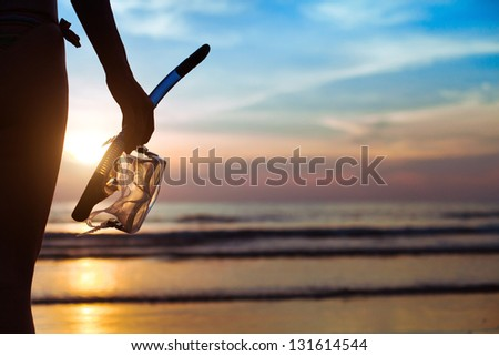 diving, silhouette of hand with equipment for snorkeling, on the beach