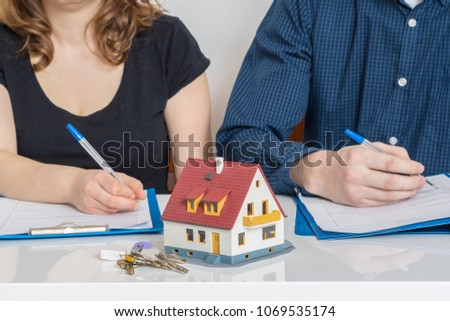 Divorce and dividing a property concept. Man and woman are signing divorce agreement. #1069535174
