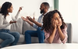 Divorce And Domestic Violence. Portrait of upset African American daughter looking through the window while her angry parents fighting in the background, depressed child feeling lonely