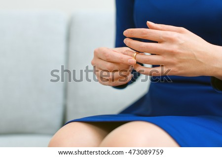 Divorce concept. Woman taking off wedding ring.