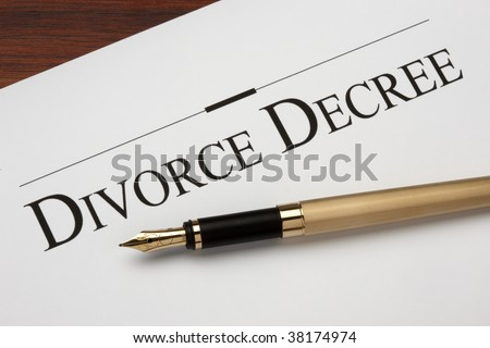 Divorce decree and gold fountain pen shot on warm wood surface