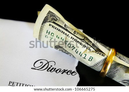 Divorce decree and rolled up cash in a wedding ring