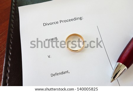 Divorce document with gold wedding ring and pen