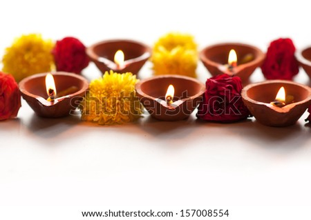Diwali Diyas in a row on a isolated white background with flowers or floral decorations