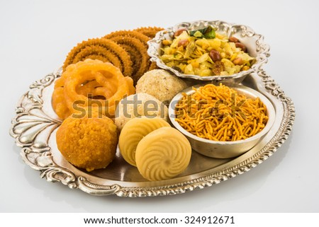 Diwali food or Diwali snacks or Diwali sweets in silver plate isolated on white background