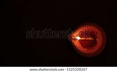 Diwali, Hindu festival of lights. Clay diya candle illuminated in Dipavali. Traditional oil lamp on dark background, copy space. Stock photo ©