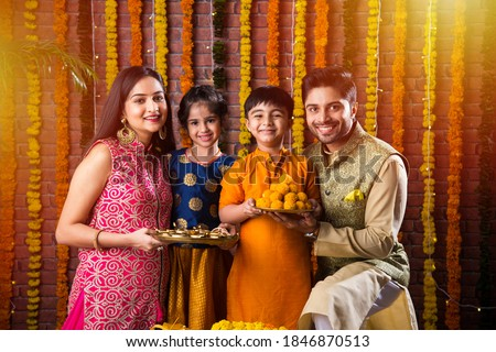 Diwali or Rakshabandhan Celebration - Indian young family of four celebrating Deepavali or bhai Dooj festival with sweet laddoo, oil lamp or diya and gift boxes, eating food or taking selfie