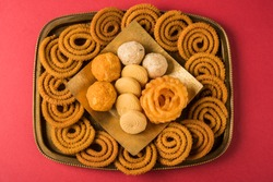 diwali snacks chakali, bundi laddu, jalebi, pedha / pera, coconut laddu in a brass tray over red background