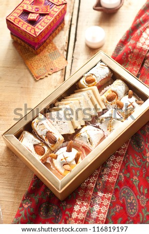 Diwali Sweets set in a Rustic India setting with rustic lamps and traditional Indian printed red cloth