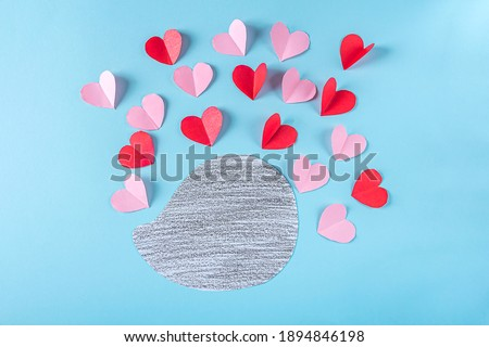 DIY and kid's creativity. Step by step instruction: how to make valentine card, hedgehog with hearts. Step3 Cutting out pink and red hearts from paper. Craft for Valentines day Foto stock ©