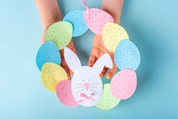 DIY and kids creativity. Step by step instruction: how to make paper easter wreath. Step11 Childrens hands holding finished cute wreath of paper eggs and bunny. Handmade Easter craft
