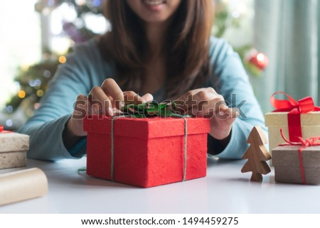 DIY art presents for christmas. Top view hands of women holding present box with red ribbon on the table and tools for wrap gift boxes.