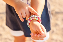DIY bracelet for children from square, round, colored beads with the words