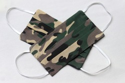 DIY camouflage fabric cloth masks in white background.  Wearing army camo or army green fabric pattern of face masks to safe outdoor activities during the coronavirus (Covid-19) pandemic.