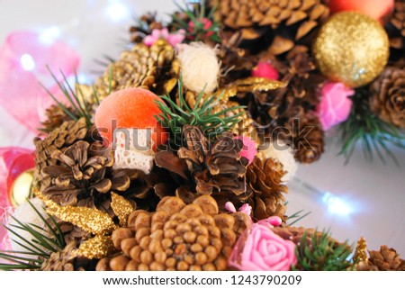 DIY Christmas wreath made of pine cones, Christmas tree decorations and New Year's decor on a light background with a garland and ornaments of cones of various sizes #1243790209