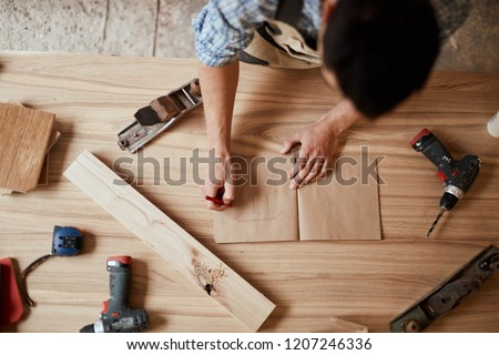 DIY concept, close up . Woodworking and crafts tools. Handicraft Carpentry. Top view of male Designer s hands working in his workshop, making a draw of custom furniture for rich people.