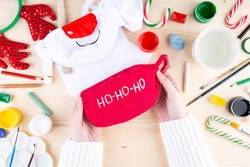 Diy festive pattern on protective mask. Step 2 drawing on red mask of the phrase santa klaus