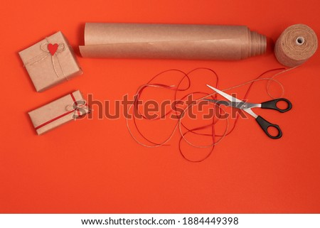 DIY gift wrapping craft paper, red ribbon, twine, scissors. 2 wrapped gifts, on a red background for valentine's day. flatly with space fot text Stock fotó ©