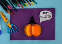 Diy Halloween card with pumpkin on purple background.Gift idea, decor Halloween.Instruction.Step by step.Top view. Children Halloween craft. Workshop.Flat lay. Step 11