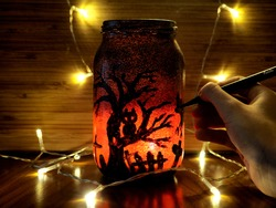 DIY Halloween lantern mason jar while painting by a hand  with pen, on wooden background with lights. Idea for room decor, decoration for halloween.