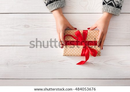DIY hobby. Woman's hands wrapping christmas or other holiday handmade present in paper with red ribbon. Give present box, decoration of gift on white wooden table, top view with copy space #484053676